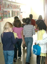 Elementary students walking in their school hallway, away from the camera