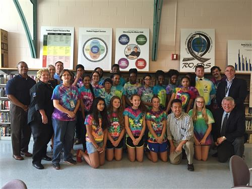 Students wearing tie dye shirts standing with Administrators in front of a bookcase